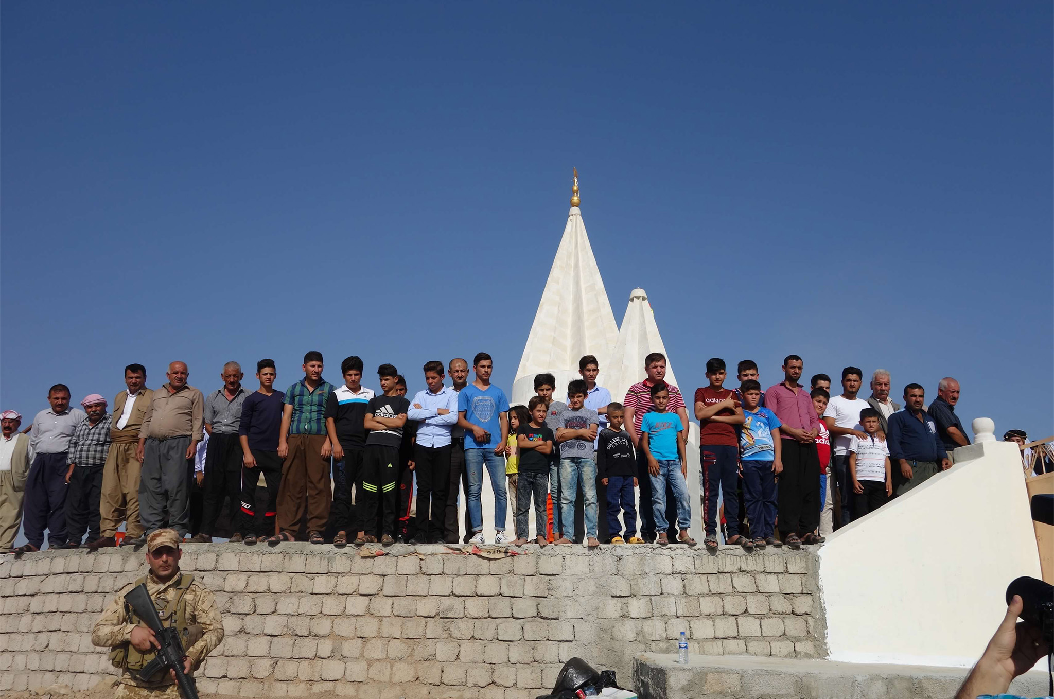 Yazidi men and boys gather at the ribbon-cutting ceremony for a reconstructed Yazidi temple in Khoshaba, Iraq, September 2017.