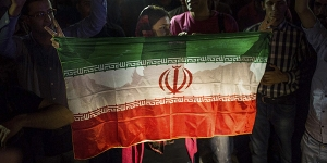 Iranians holding their flag celebrate the announcement that Iran had reached a nuclear deal with world powers in Tehran, Iran, July 14, 2015. Iran and a group of six nations led by the U.S. said they had reached a historic accord on Tuesday to significantly limit Tehran's nuclear ability for more than a decade in return for lifting international oil and financial sanctions.