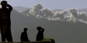 Eastern Shura fighters watch as U.S. B-52's carpet bomb an area of the Tora Bora mountains in Afghanistan