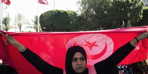 A protester carries a Tunisian flag during a rally after the assassination of Mohamed Brahmi, the leader of the Arab nationalist People's Party, on Avenue Habib Bourguiba in Tunis, Tunisia, July 25, 2013. The killing of Mohamed Brahmi incited protests blaming the ruling party, as the birthplace of the Arab Spring plunged again into crisis. (Gianni Cipriano/The New York Times)