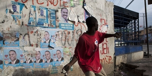 A protester hurls a rock at United Nations peacekeepers outside the electoral board offices in Port-au-Prince, Haiti, on Dec. 8, 2010. Angry protesters torched the headquarters of the government-backed presidential candidate and blocked streets with rubble from earthquake-destroyed buildings hours after the late-night release of preliminary election results triggered violence and new questions about vote rigging.