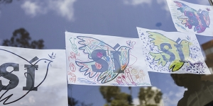 """Artwork of doves with the Spanish word for """"yes,"""" urging support for a coming referendum, in the window of a kindergarten on the day of the signing of a peace agreement between the Colombian government and the Revolutionary Armed Forces of Colombia, or FARC, in Bogota, Sept. 26, 2016. In a moment that generations of Colombians yearned to see, the state and Marxist insurgents confirmed an accord to end a 52-year-old conflict, the last major war in the Americas. (Federico Rios Escobar/The New York Times)"""