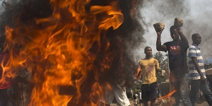 On election day, a crowd sets a fire and uses large cobblestones to make a roadblock in the Nyakabiga neighborhood after the body of an opposition activist was found dead in a ditch, in Bujumbura, Burundi, July 21, 2015. At several polling stations around Bujumbura, the capital, turnout was low Tuesday morning, with voters outnumbered by campaign workers and police officers. (Tyler Hicks/The New York Times)