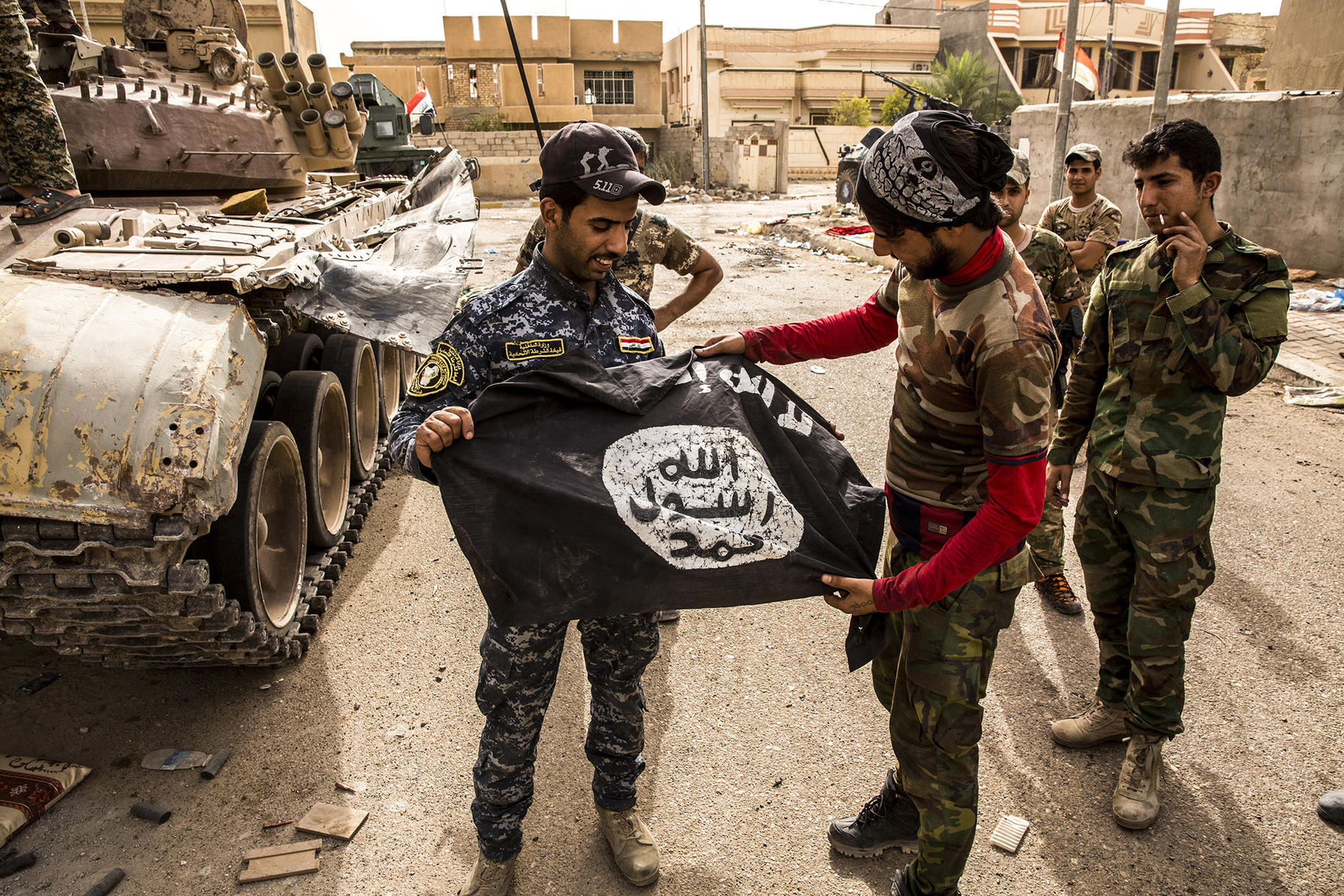 A member of the Iraqi federal police, left, and forces loyal to the Iraqi government displayed a captured Islamic State flag in the Nazal district of Fallujah, Iraq. (Bryan Denton/The New York Times)