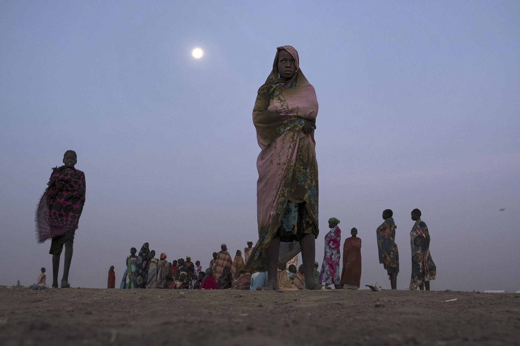 Women wait early in the morning at a water collection point in Bentiu, the country's largest camp for displaced people, in South Sudan. (Tyler Hicks/The New York Times)