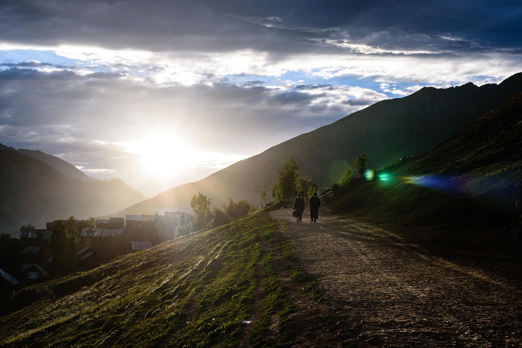 Men walk home as the sun sets over Budogam village, in the Tulail Valley in India, in the state of Kashmir. (Michael Benanav/The New York Times)