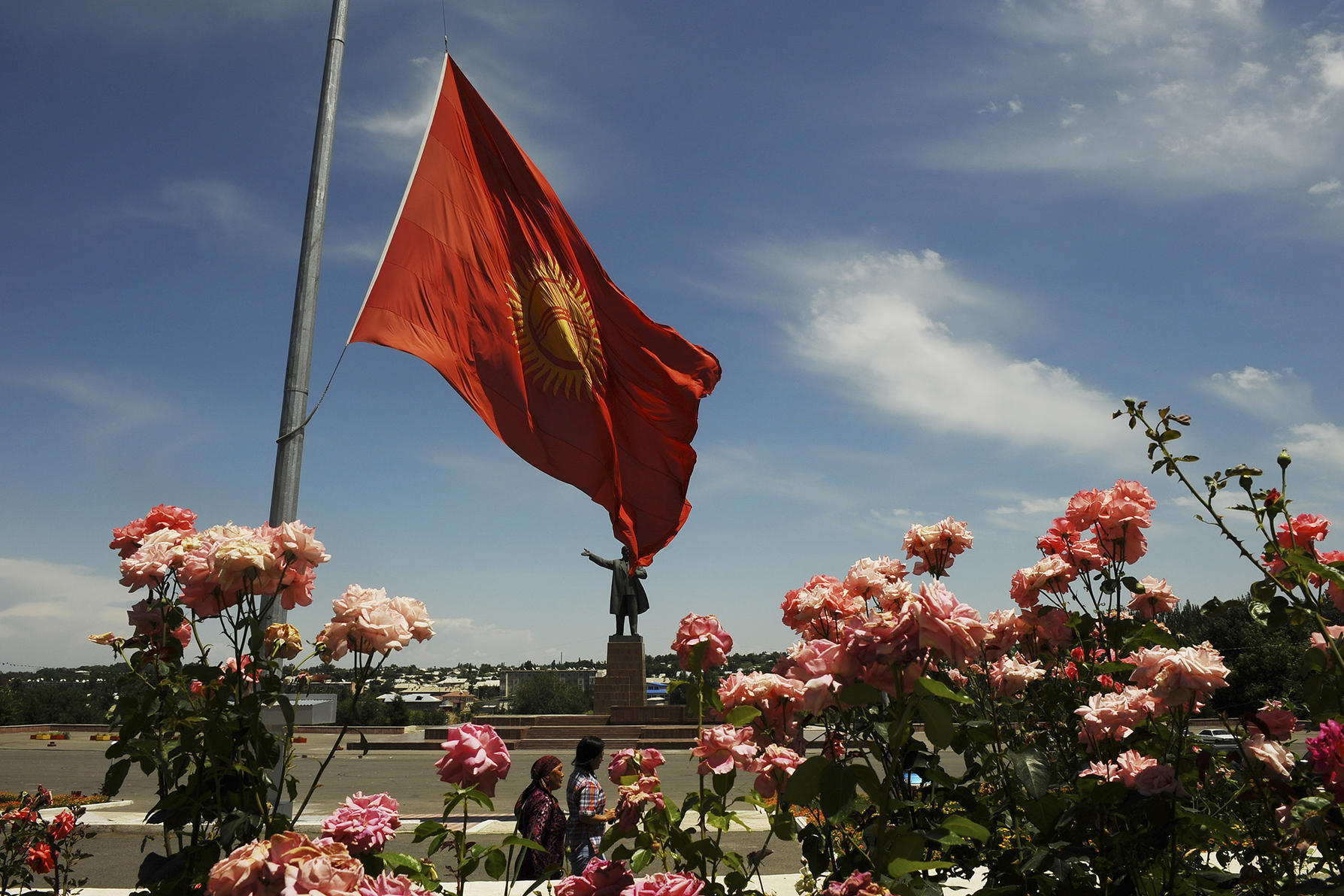 The Kyrgyzstan flag flies at half mast outside the Osh town hall as people walk through the still largely vacant city in Kyrgyzstan, June 19, 2010. (James Hill/The New York Times)