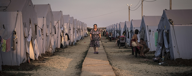 A woman walks among the tents at a refugee camp in Donetsk, Aug. 22, 2014. The United Nations reports that more than a million Ukrainians have been displaced by war. (Sergey Ponomarev/The New York Times)