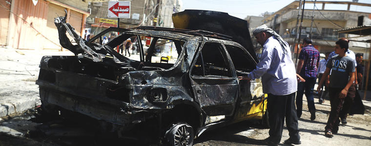 A damaged car after a bombing attack in Baghdad.