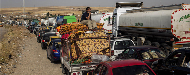 People leaving areas controlled by the Islamic State in Iraq and Syria wait to clear the Khazer checkpoint between Mosul and Erbil in Iraq, June 14, 2014. Photo Credit: The New York Times/ Bryan Denton