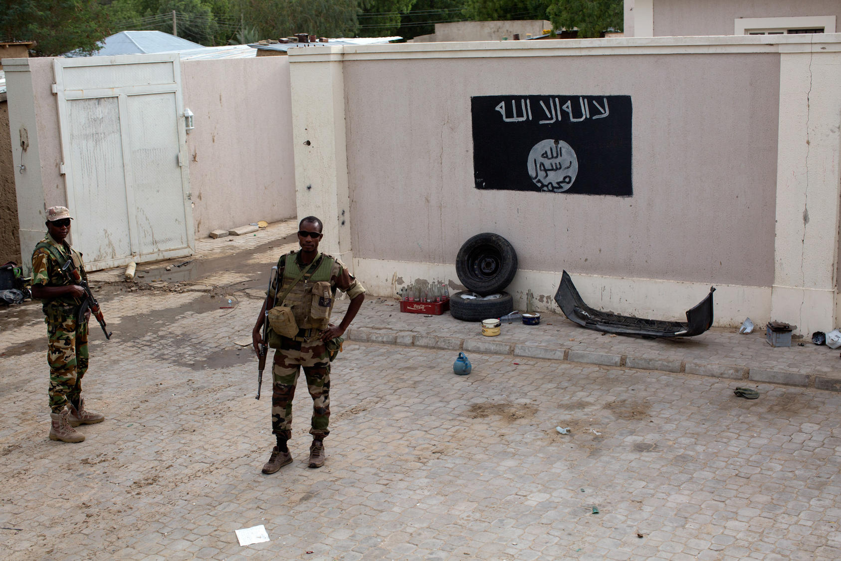 Chadian soldiers stand near a Boko Haram flag, one of many in the now-liberated — and deserted — city of Damasak, in northern Nigeria, March 18, 2015. Though the Nigerian government insists its forces have chased Boko Haram out if much of its territory, only soldiers from Chad and Niger were involved in liberating this once-thriving city of 200,000.