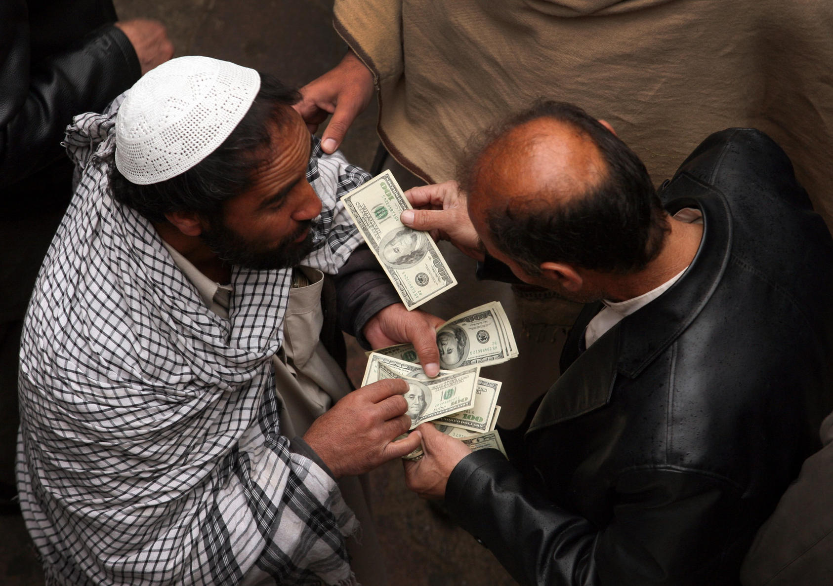 Men negotiate money exchanges at a market in Kabul, on Jan. 29, 2011. The large, informal, market is crucial to the economy in a country where many of the poor do not use banks. Potential losses of as much as $900 million at the Kabul Bank could deepen distrust of banks in the country. (Michael Kamber/The New York Times)
