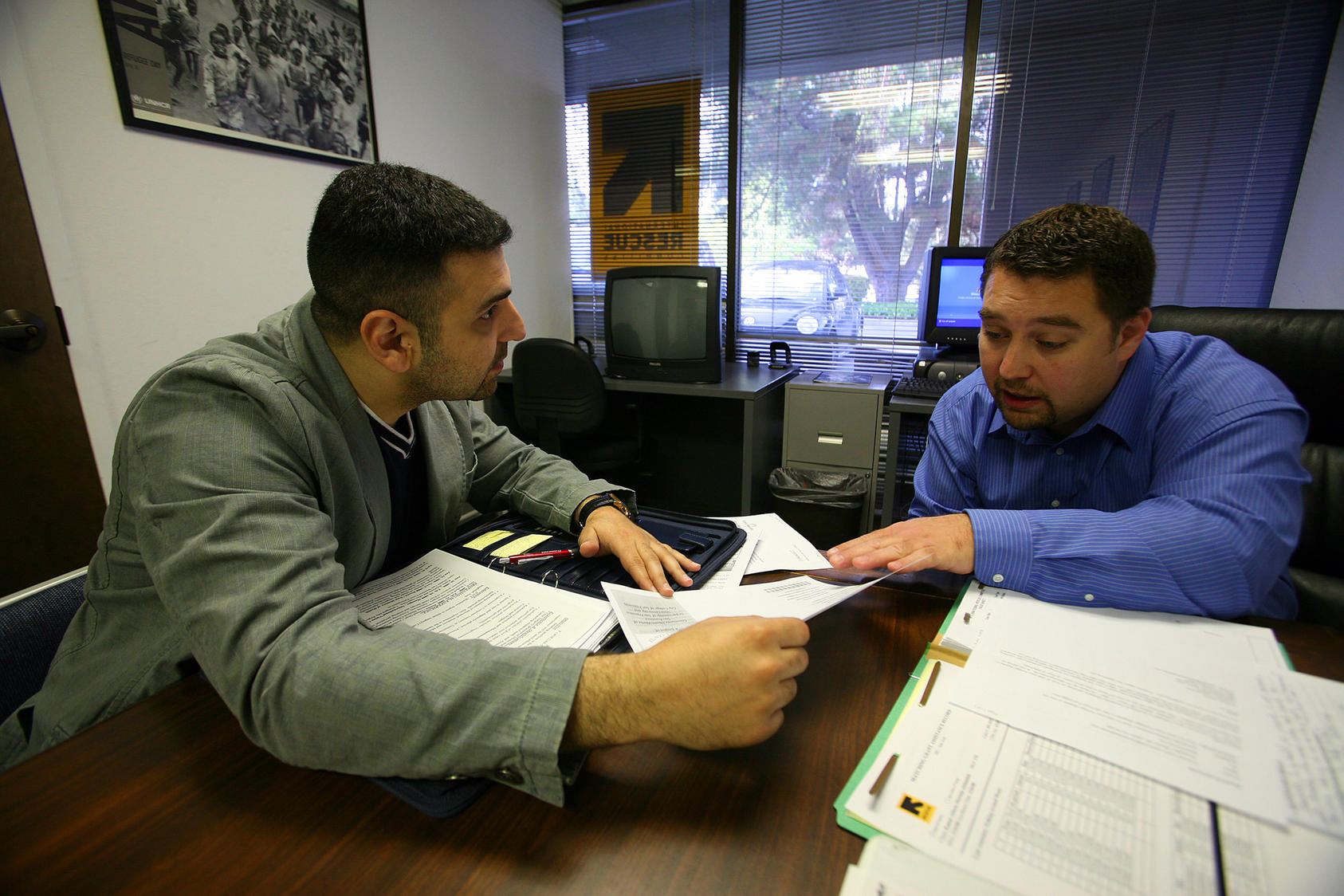 26-year-old Iraqi refugee, left, working on his resume with Sead Eminovic