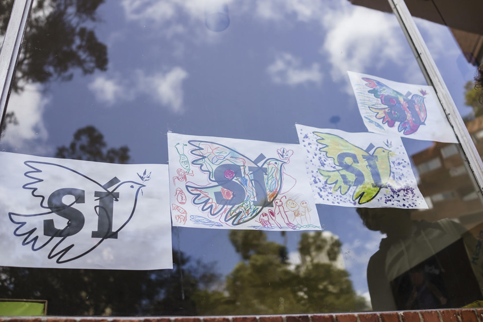"Artwork of doves with the Spanish word for ""yes,"" urging support for a coming referendum, in the window of a kindergarten on the day of the signing of a peace agreement between the Colombian government and the Revolutionary Armed Forces of Colombia, or FARC, in Bogota, Sept. 26, 2016. In a moment that generations of Colombians yearned to see, the state and Marxist insurgents confirmed an accord to end a 52-year-old conflict, the last major war in the Americas. (Federico Rios Escobar/The New York Times)"
