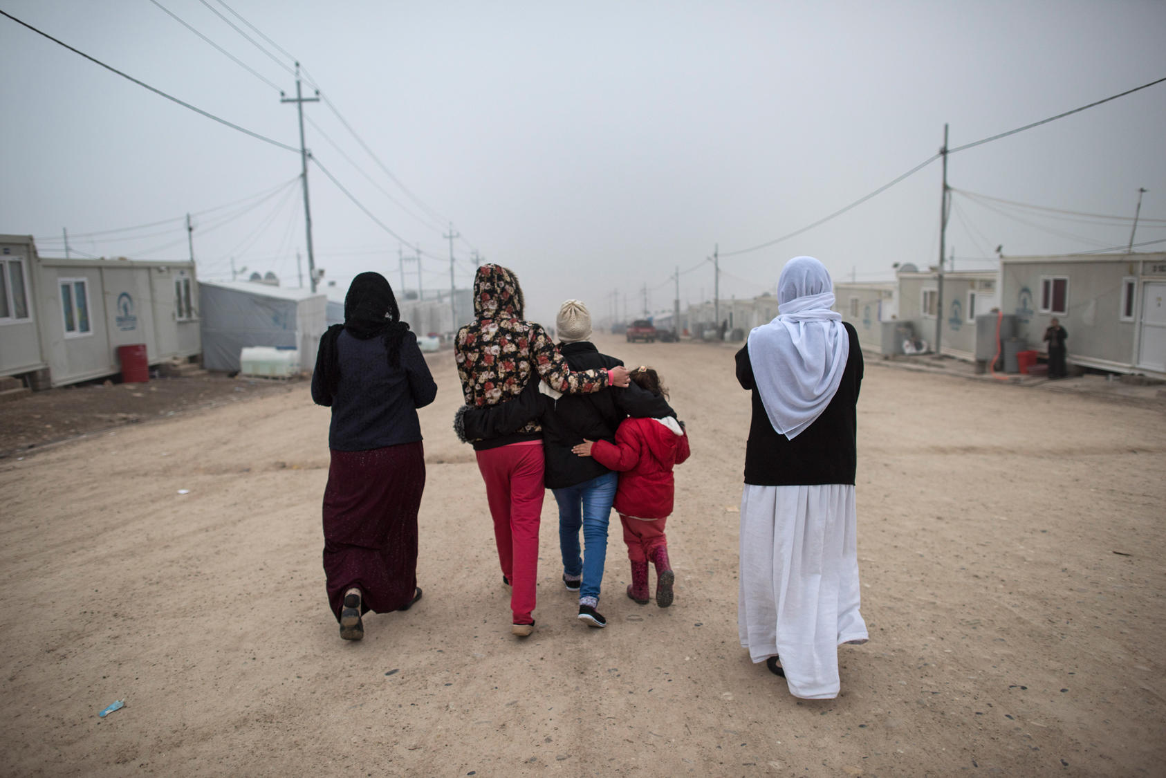 """M."", center, a Yazidi teen who escaped sex slavery under the Islamic State group, is comforted by relatives before leaving to be resettled in Germany, at a camp near Dohuk, Iraq, Jan. 24, 2016. Islamic State leaders have made sexual slavery integral to the group's operations, aggressively pushing birth control on the victims to keep the trade running. (Lynsey Addario/The New York Times)"