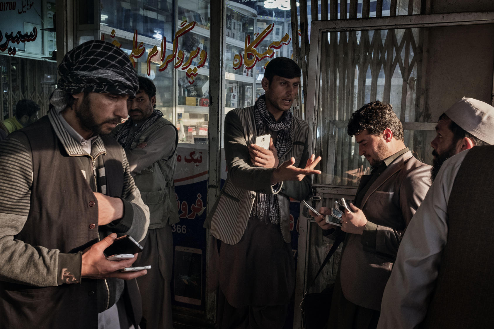 Afghans buy and sell used and new mobile phones, SIM cards and phone credit cards at a market in Kabul, Afghanistan, March 31, 2016. The local telecommunications industry was a rare economic bright spot, but losses are now mounting as new taxes are imposed and a dwindling pool of customers as American troops and foreign contractors leave.