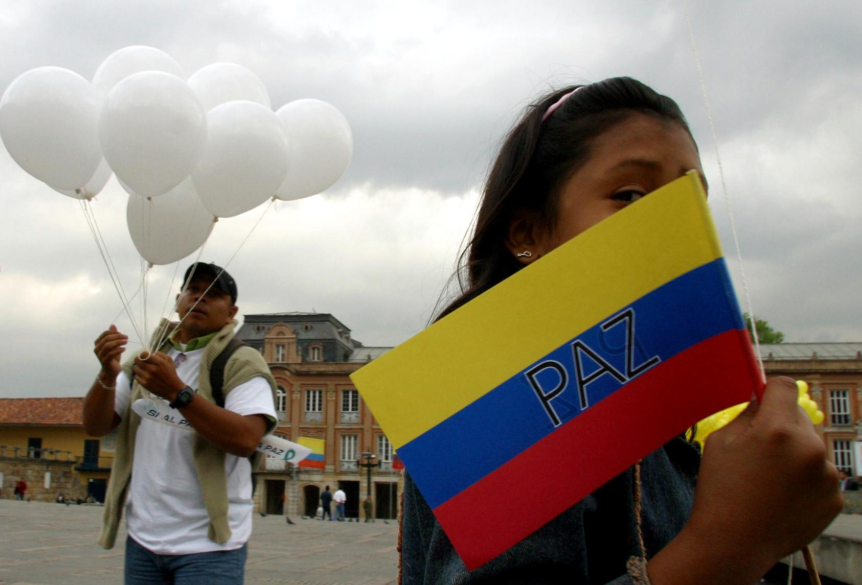 "A young girl holds a Colombian flag that reads ""Peace"" in front of the Congress building where Salvatore Mancusso, paramilitary leader of the supreme commander of the United Self-Defense Forces was speakingM Wednesday, July 28, 2004 in Bogota, Wednesday, July 28, 2004. Mancuso addressed lawmakers for the first time about the peace process between the AUC and the Colombian government. (Scott Dalton/The New York Times)"