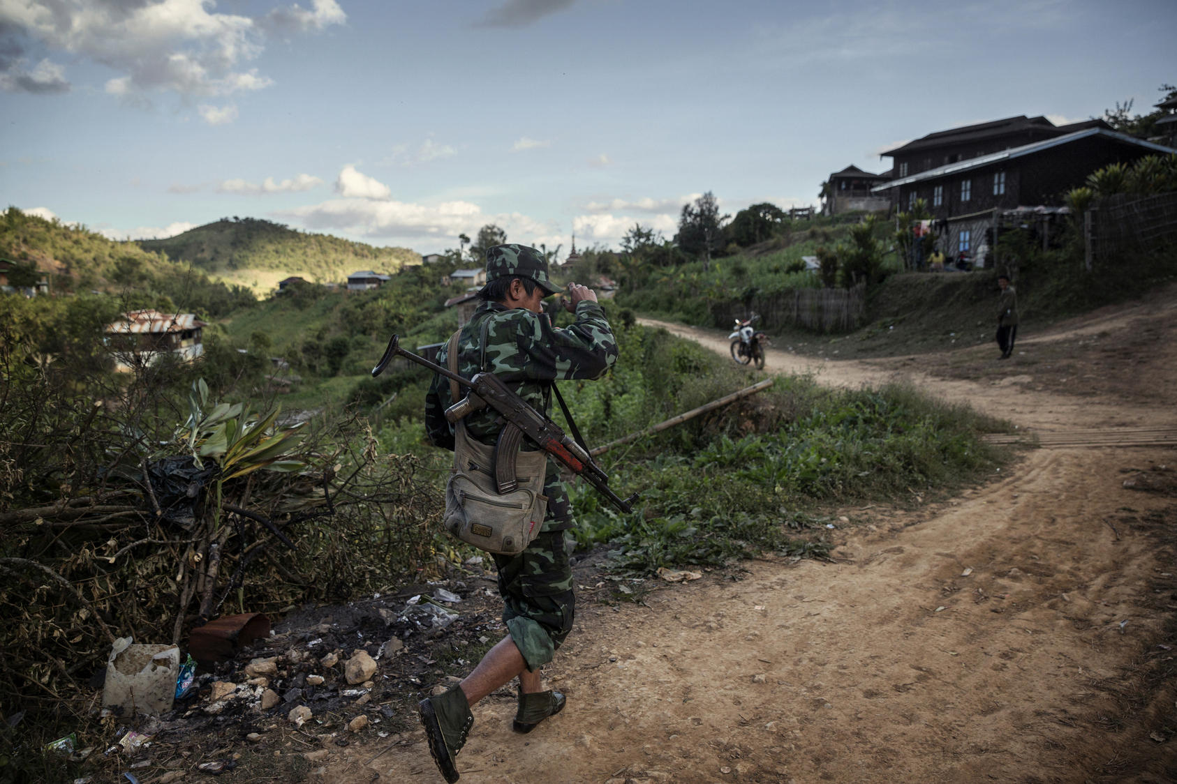 A Shan State Army - South rebel soldier walks through Bang Laem Village, Shan State, Myanmar, an area where poppy farming has flourished, Dec. 7, 2014. Growing opium poppies is illegal in Myanmar, but small-scale farmers see it is a relatively low-risk cash crop.
