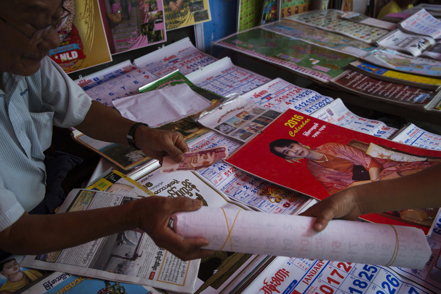 A woman purchases a calendar of Aung San Suu Kyi – who says she plans to circumvent the ban on her becoming president that the generals wrote into the Constitution – in Yangon, Myanmar, Nov. 10, 2015. Vestiges of Myanmar's police state, alive and well, will wield enormous influence even with the lopsided election triumph by Aung San Suu Kyi's Party.