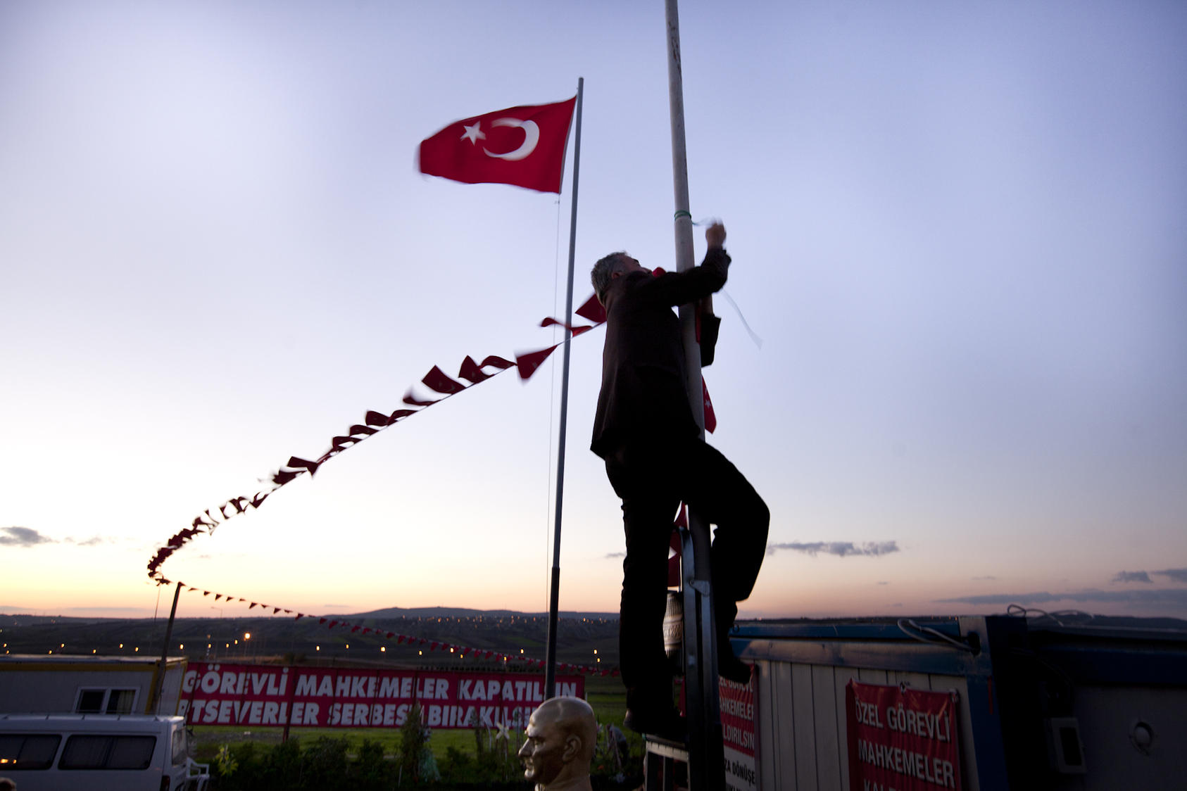 A man ties flags around a pole at a protest camp outside a prison and courthouse in Silivri, Turkey, Nov. 8, 2012. Secular protesters have set up a camp to protest the trial of hundreds of military officers charged with plotting to overthrow the Islamic-rooted government.
