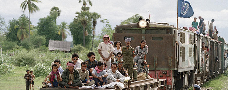 Cambodians returning from refugee camps in Thailand aboard a UNHCR (Office of the United Nations High Commissioner for Refugees) train as it approaches Phnom Penh. June 1992
