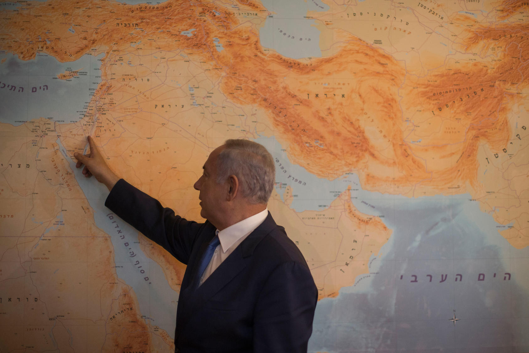 Prime Minister Benjamin Netanyahu with a floor-to-ceiling map that has Israel at its center, in his office in Jerusalem, July 2016. Photo Courtesy of The New York Times/Uriel Sinai