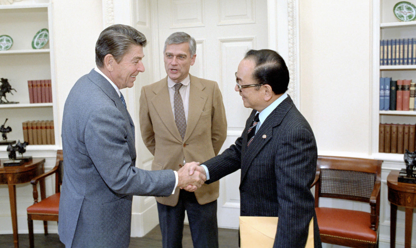 As senators, former World War II lieutenants Spark Matsunaga of Hawaii, right, and Mark Hatfield of Oregon, center, join President Ronald Reagan in 1984 to formally establish the U.S. Institute of Peace.  (The White House)