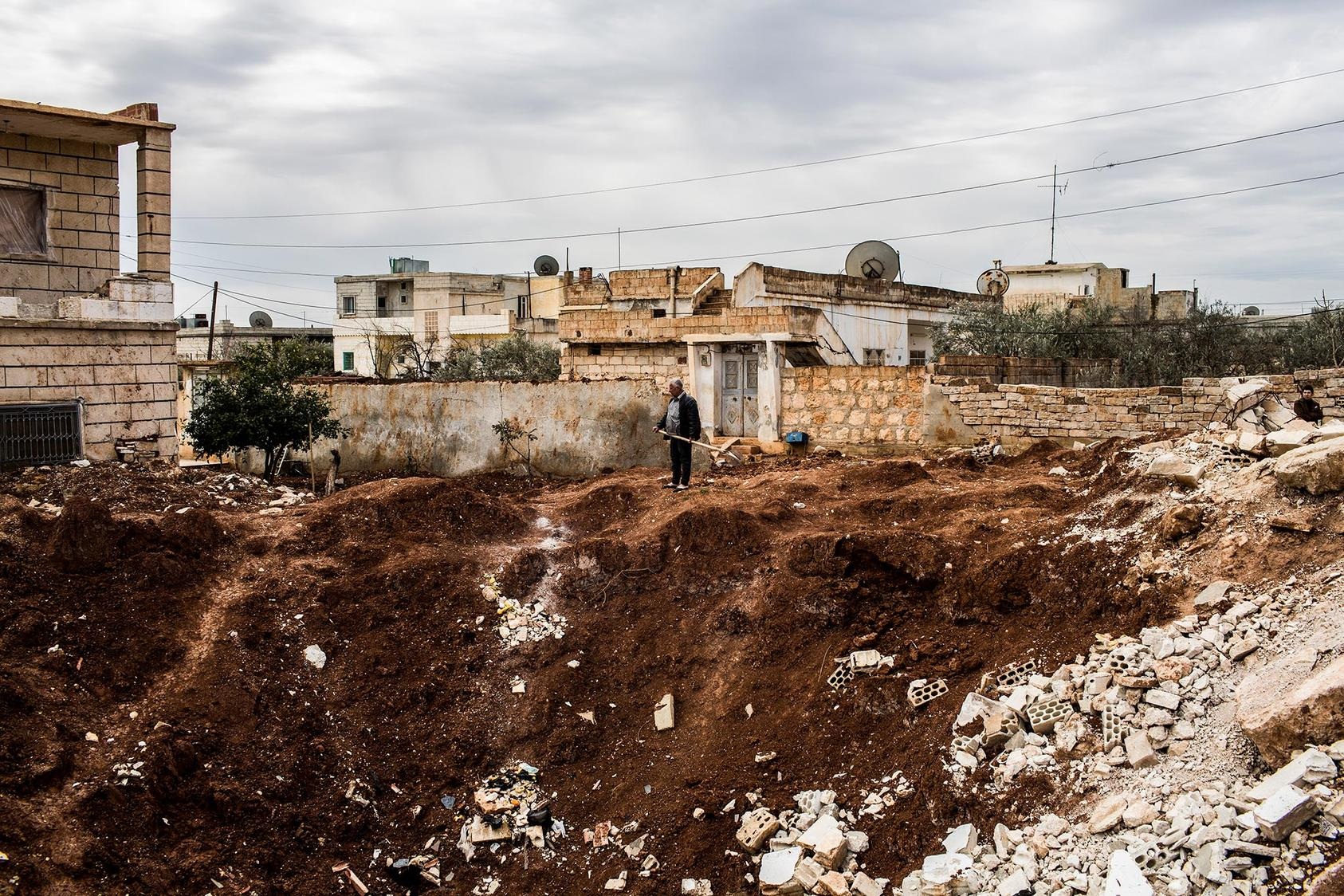A man holding a shovel surveys a crater left by what locals said was a Scud missile strike