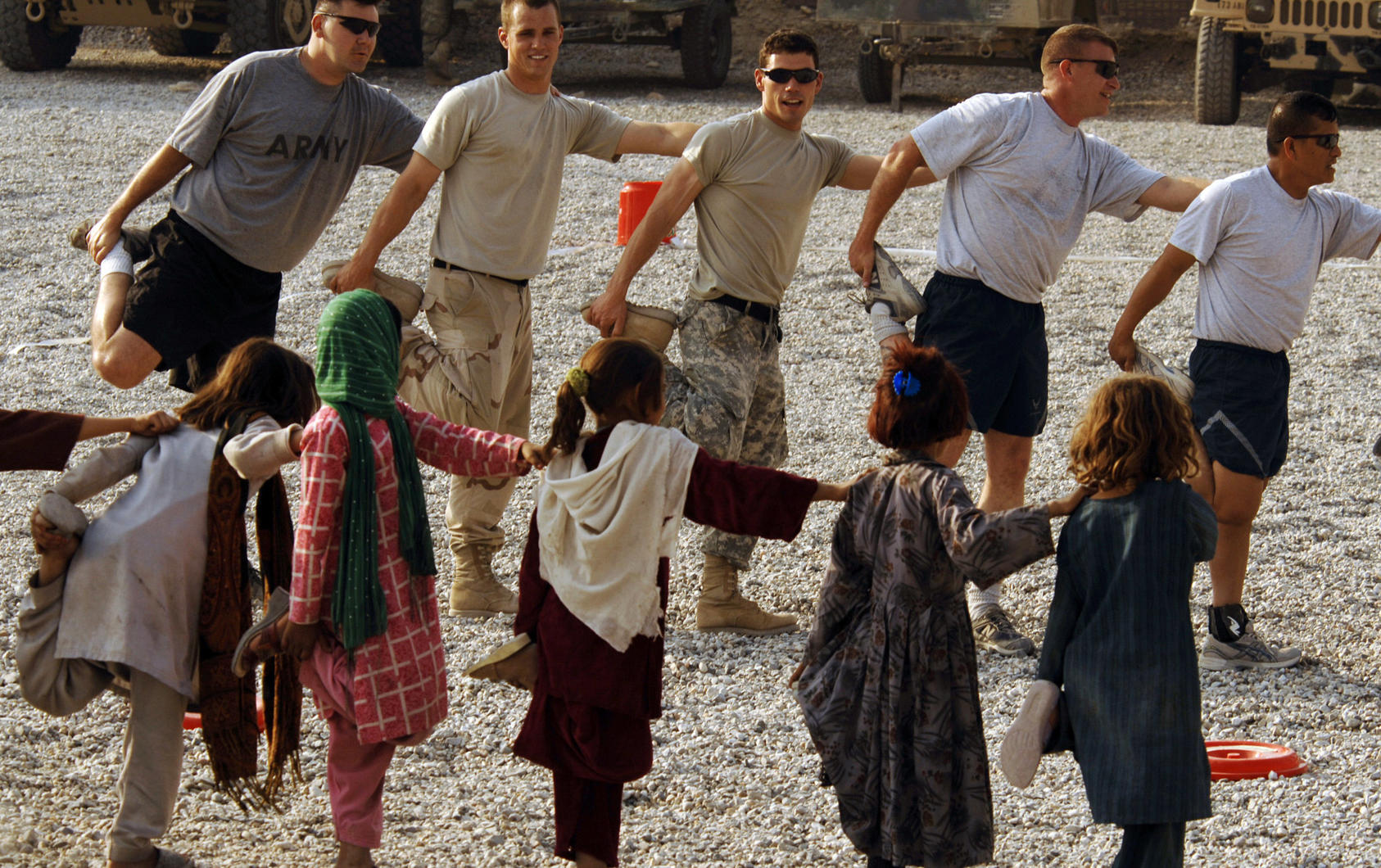 U.S. Army and Air Force personnel and local children stretch before a soccer game at the Nangarhar Provincial Reconstruction Team Forward Operating Base in Jalalabad, Afghanistan.