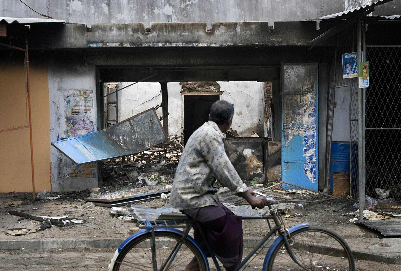 A man bicycles on May 7th, 2006, past Tamil-owned stores that were set ablaze by a Sinhalese mob in Trincomalee, Sri Lanka. April was the bloodiest month since the government and the separatist Liberation Tigers of Tamil Eelam signed a cease-fire in February 2002 that was supposed to end nearly two decades of killing here.