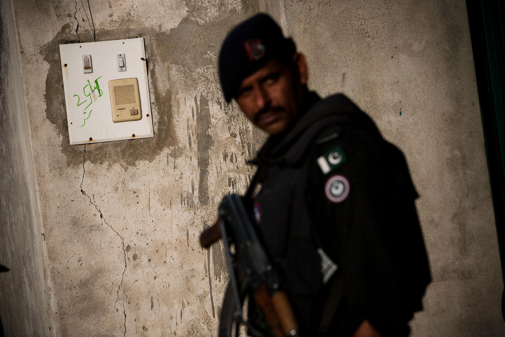 A Pakistani policeman stands next to the intercom at the entrance to the compound where Osama Bin Laden was killed in Abbottabad, Pakistan.