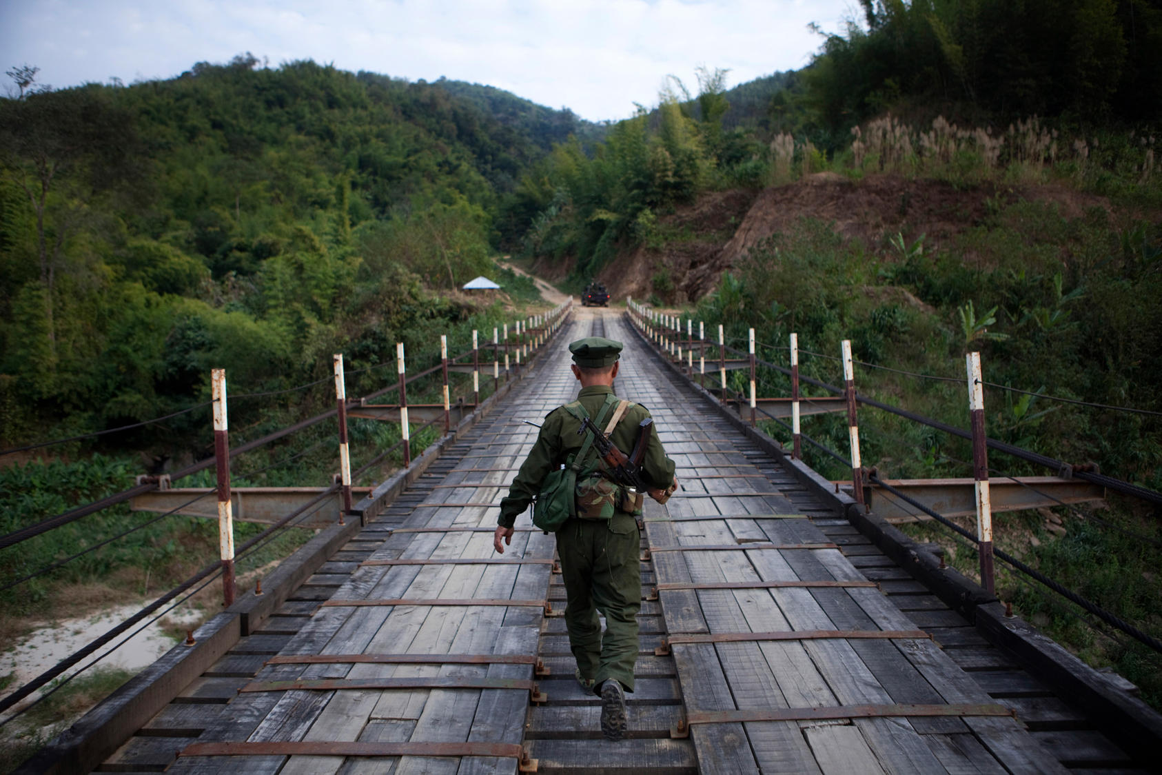A Kachin Independence Army soldier travels across a bridge to the front lines between Laiza and Maija Yang in Myanmar, Jan. 9, 2012.