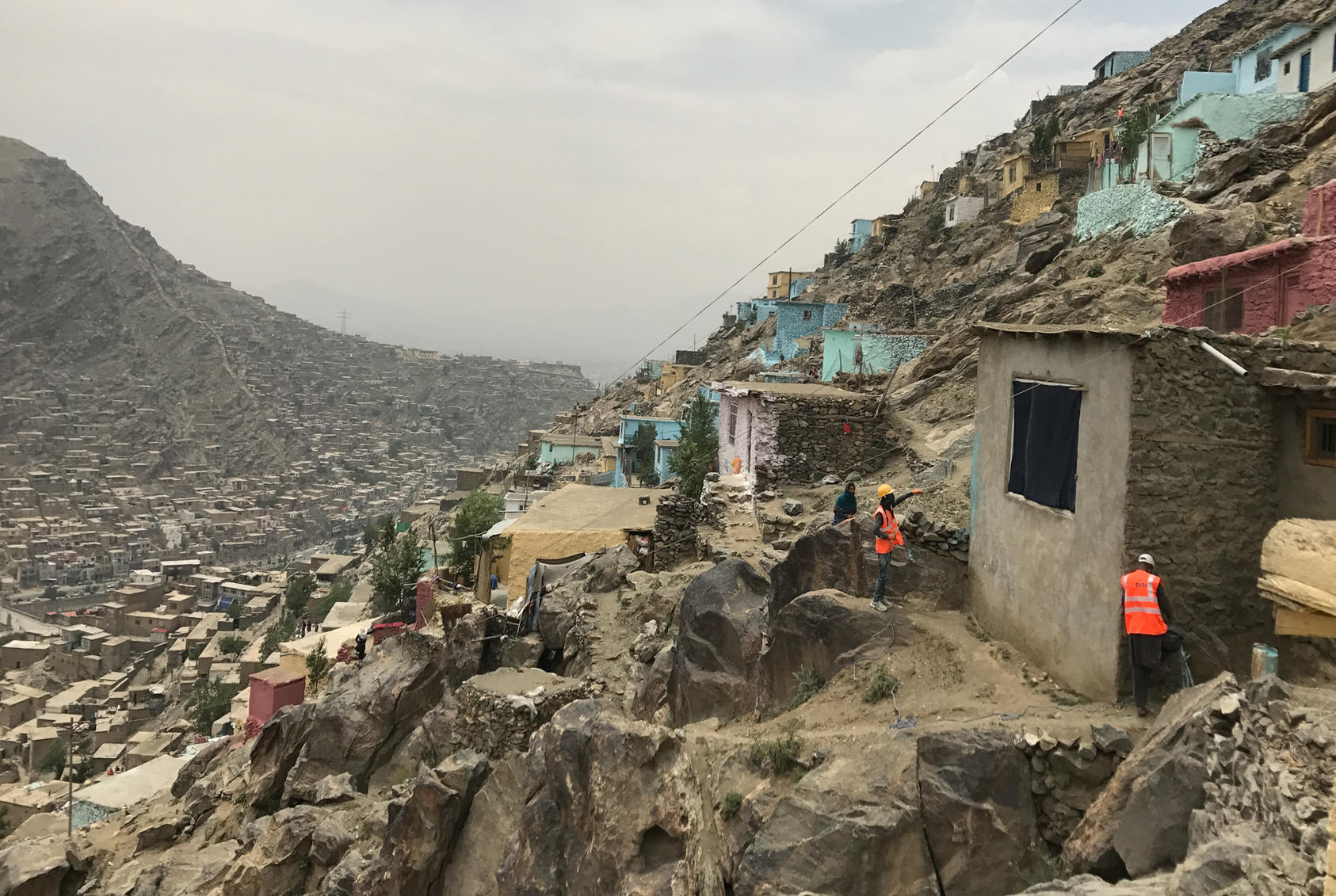An undated photo of painters beginning to add color to the front of a home on a hillside in Kabul, Afghanistan, an attempt by the municipality to make the sprawl look nicer. The city, one of the fastest growing in the world, has already expanded to more than five times its intended size.