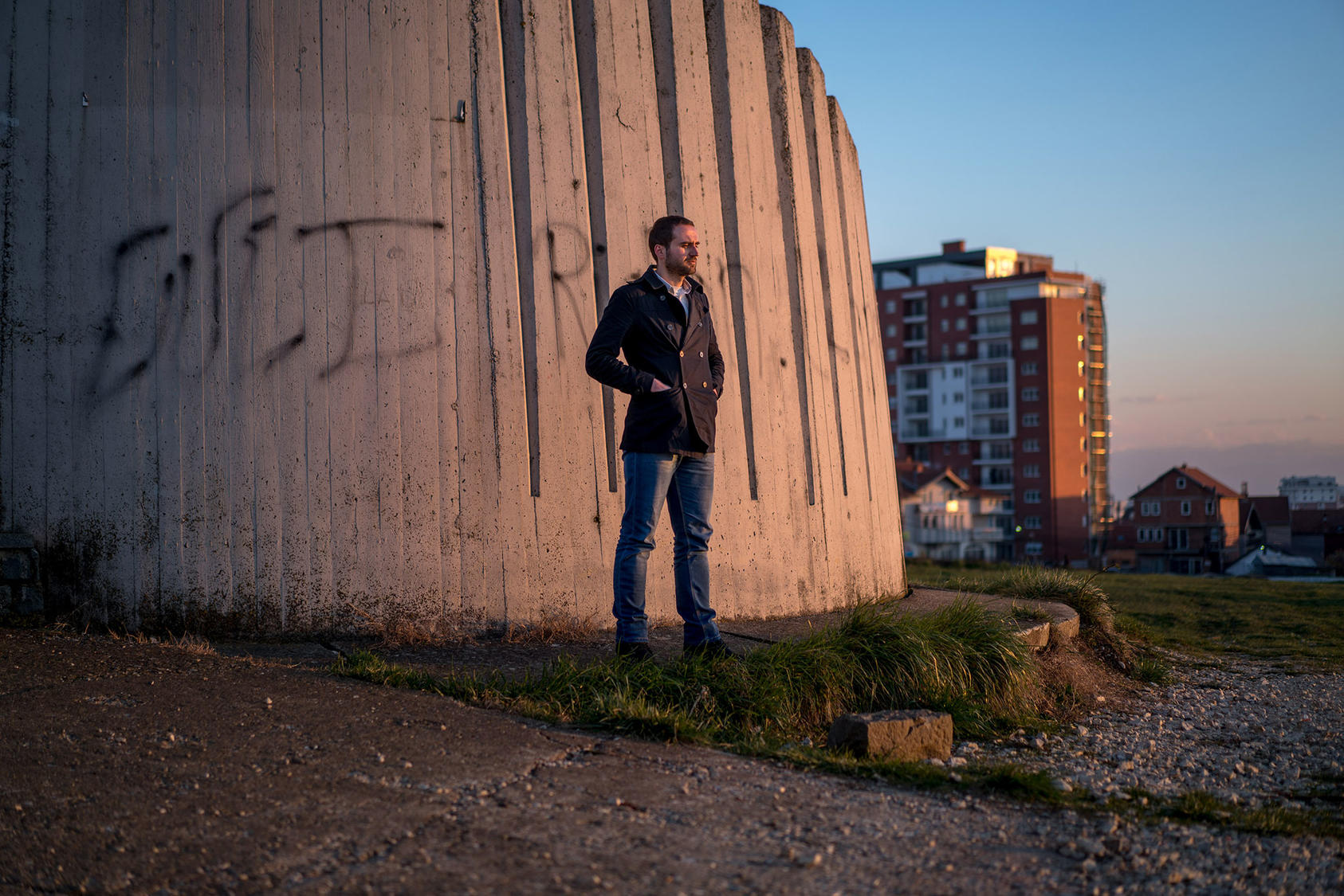 man standing outside prison wall in Pristina, Kosovo