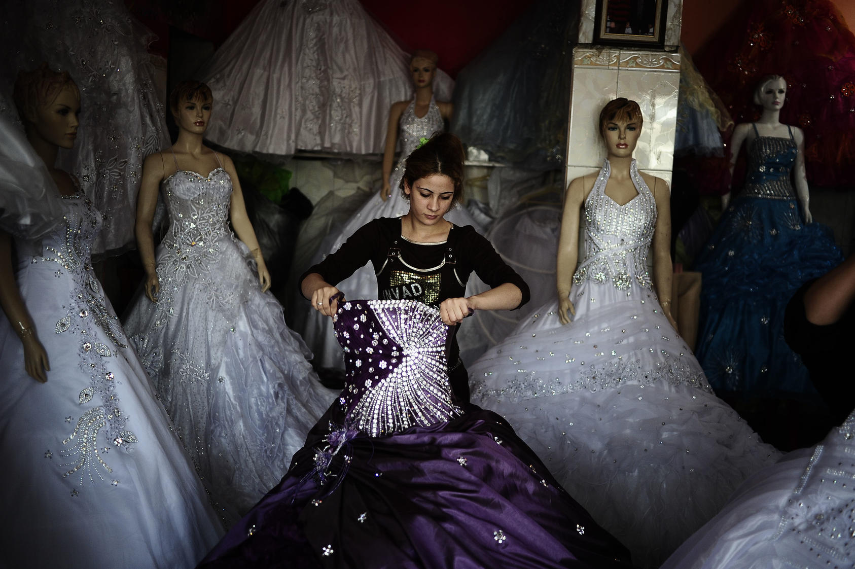 A woman works in a shop that rents wedding dresses in the Sadr City neighborhood of Baghdad.