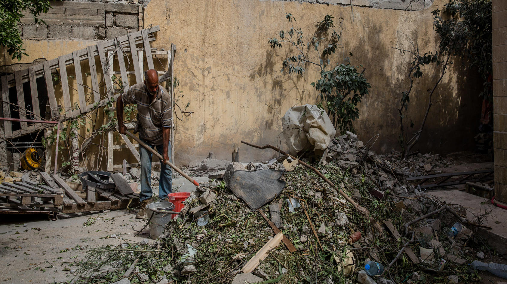 A man clears rubble from his front yard after it was damaged by an airstrike in the Rifai neighborhood of Mosul, Iraq, May 19, 2017.