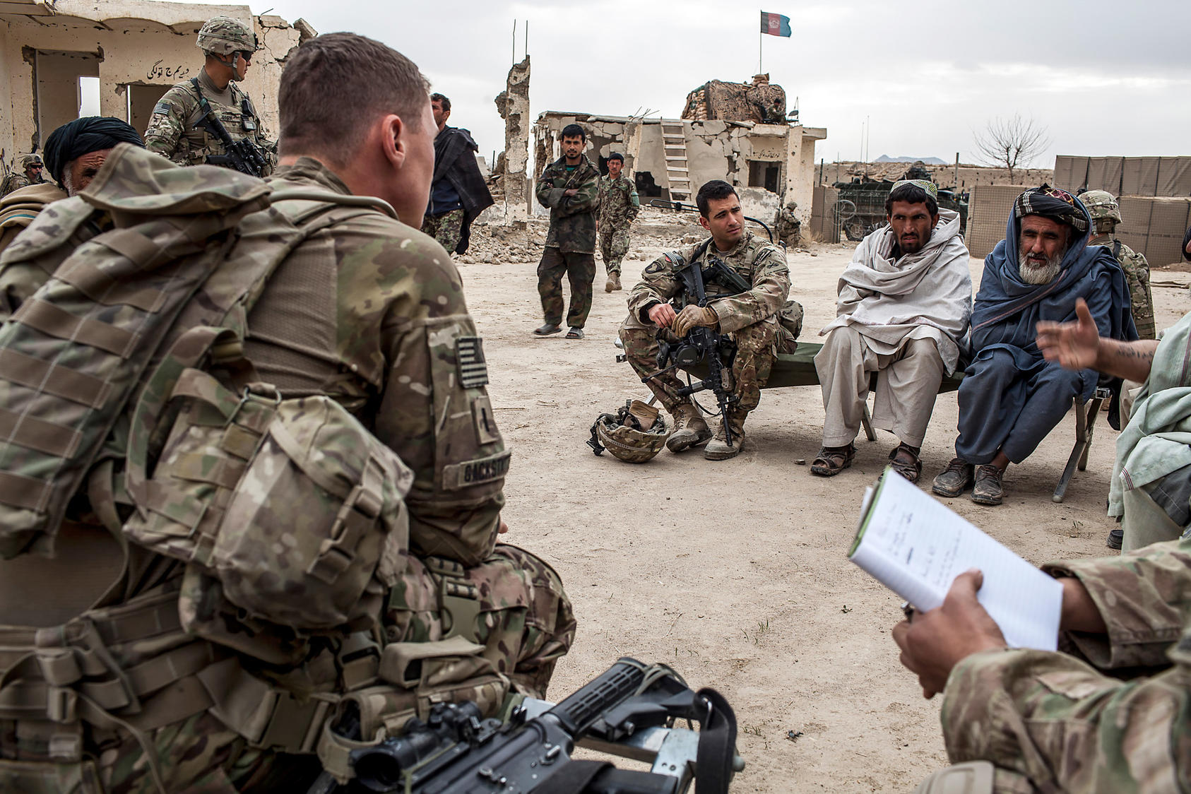U.S. Army Capt. Aaron Daniele sits next to elders from the village of Tieranon in Pashmul, Afghanistan, in an effort to establish an Afghan Local Police unit in their village