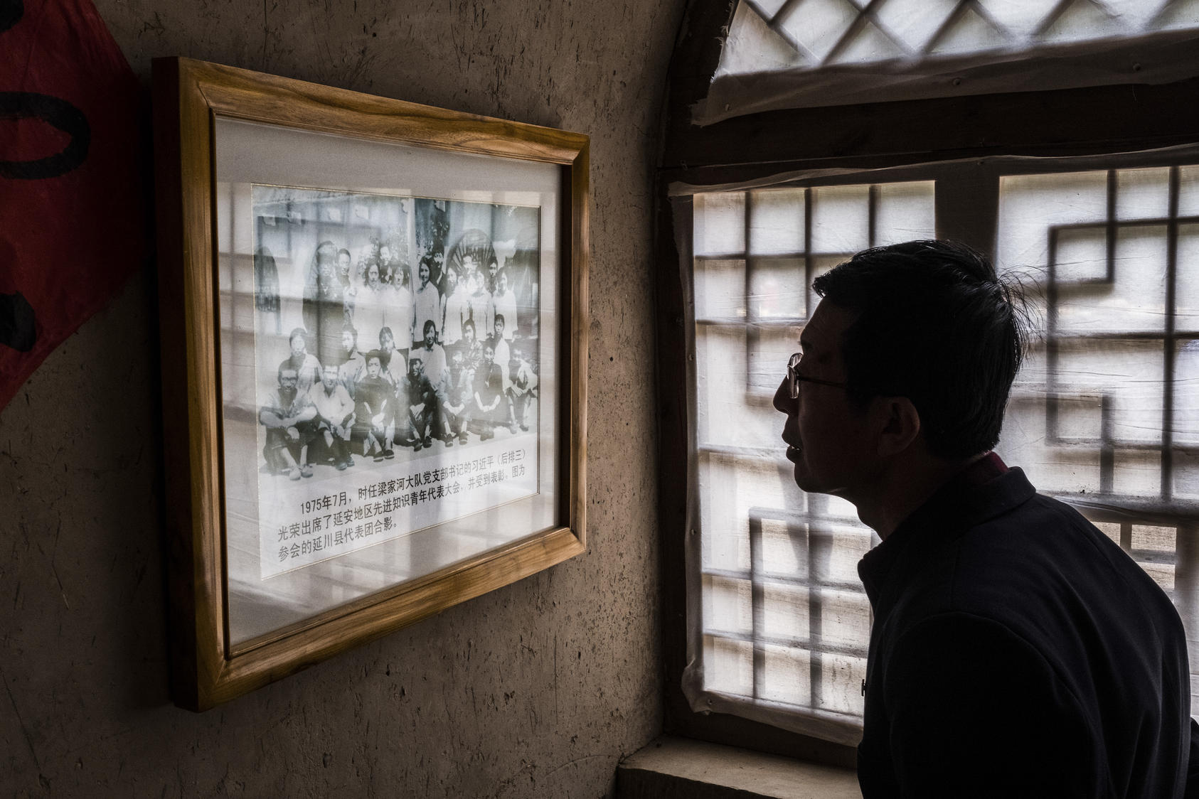 A visitor looks at a photo of a young Xi Jinping with party members, in Liangjiahe, China. The village, where Xi spent a formative period of his youth during the Cultural Revolution, has been converted into a tourist attraction. Photo NYT/Bryan Denton