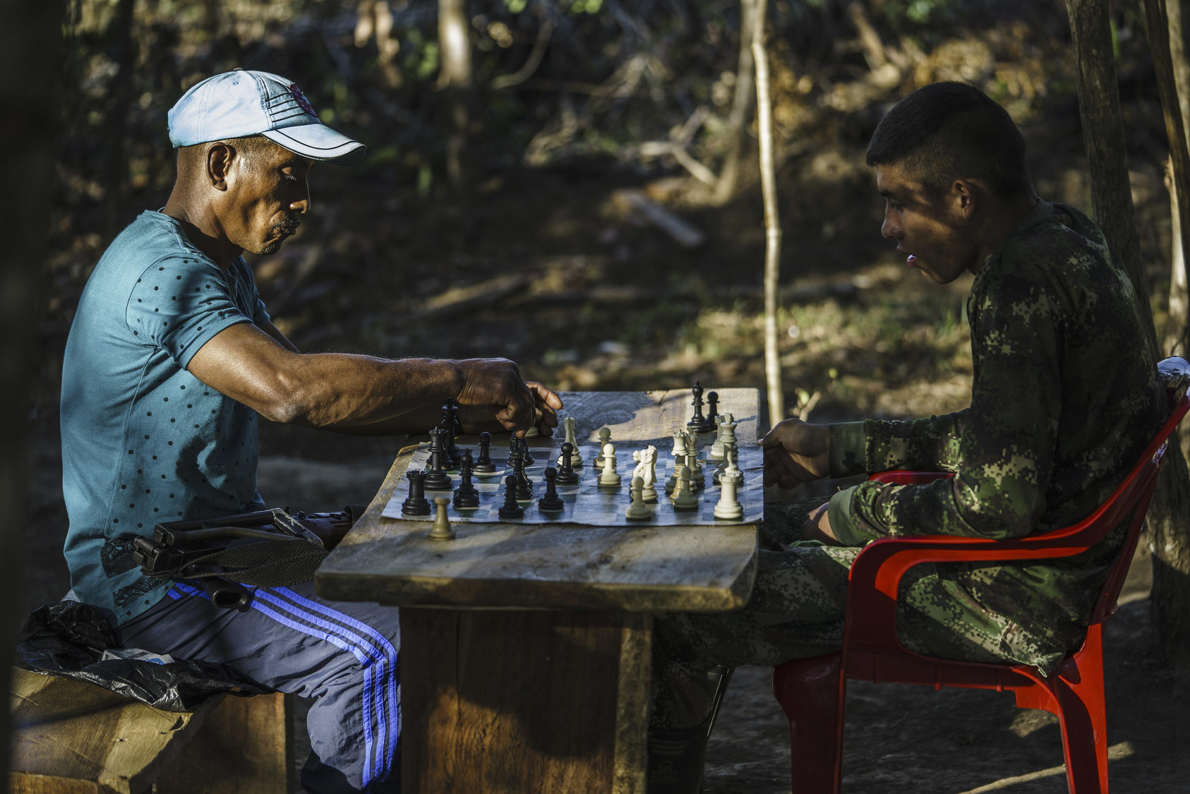 FARC members play chess in one of the zones set up to transition the former rebels back to civilian life, near La Paz, Colombia, Feb. 1, 2017. As the peace process moves ahead, mixed feelings in towns like La Paz are clear evidence of lingering divisions and bitter memories of the conflict. (Federico Rios Escobar/The New York Times)