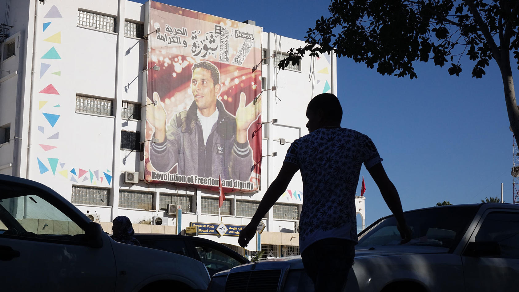 In the Tunisian city of Sidi Bouzid, cars and pedestrians bustle past the post office, with its portrait of street vendor Mohammed Bouazizi, whom Tunisians describe as a martyr to their democracy.