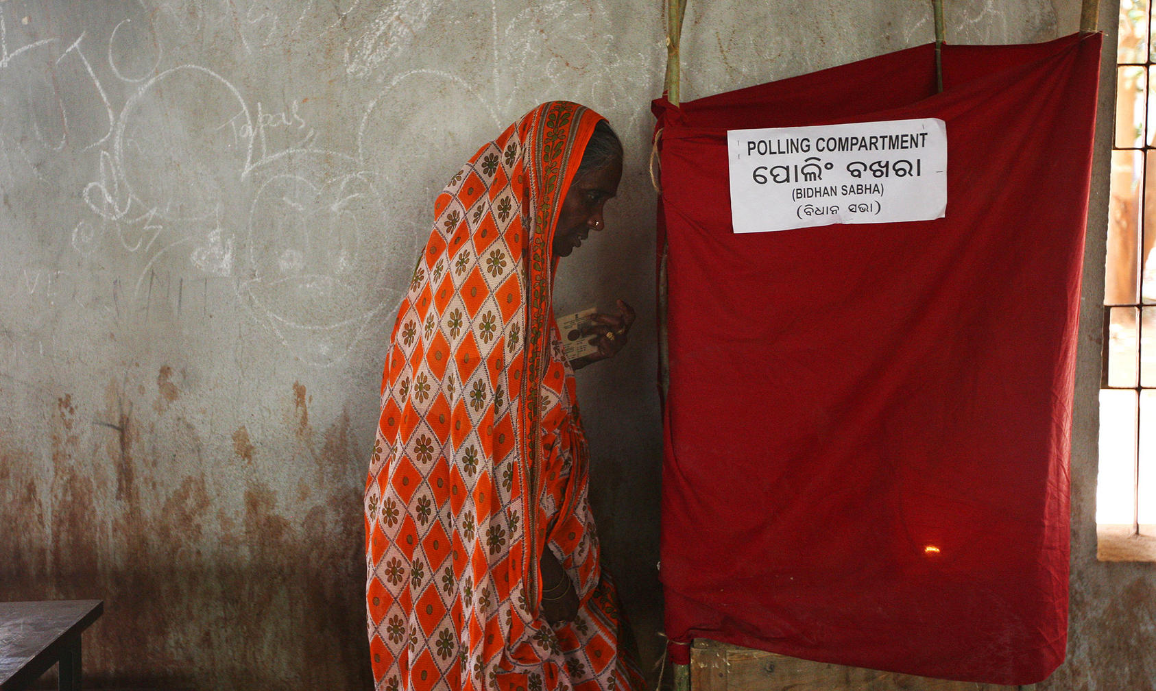 A woman enters a booth to mark her ballot at a polling station in the city of Bhubaneswar, in the state of Orissa