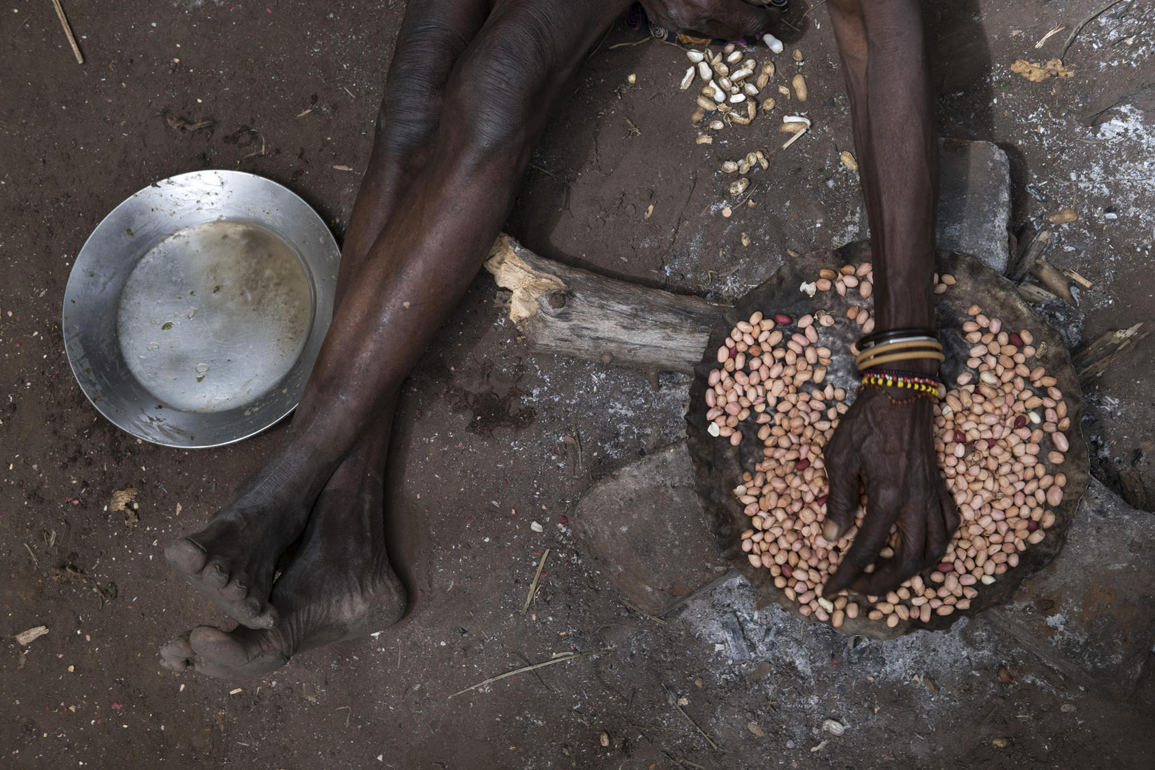 A woman roasts peanuts in South Sudan, Feb. 2017. The U.N. declared that parts of South Sudan were suffering a famine, a direct result of the ethnic feud between the Nuer and Dinka that is spiraling into a civil war. Photo Courtesy of the NYT/Tyler Hicks