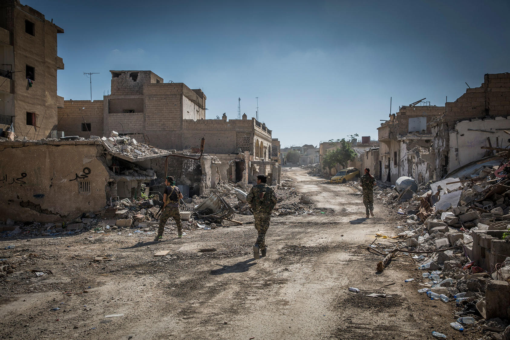 Soldiers with the Syrian Democratic Forces move through the destroyed streets of east Raqqa