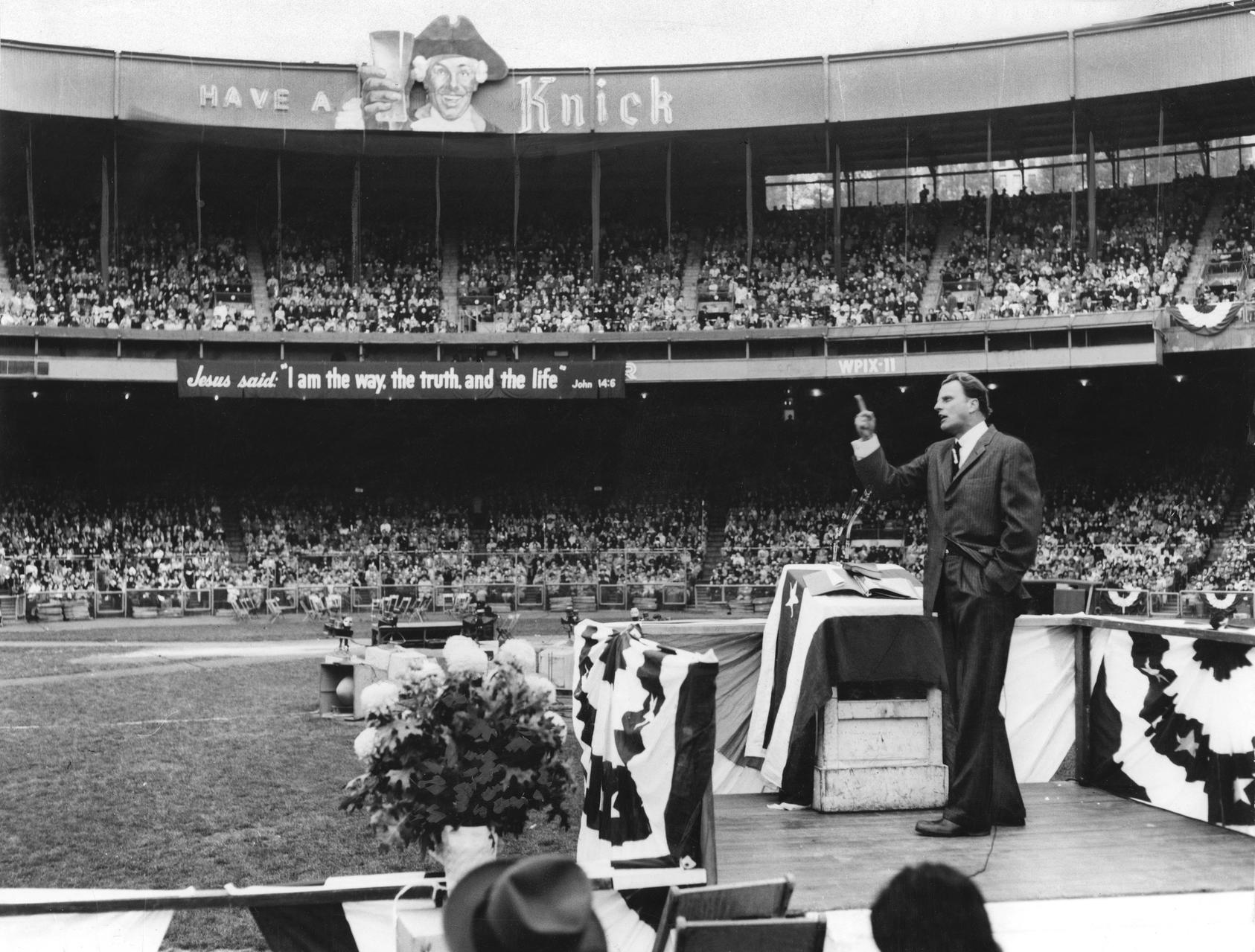 Reverend Billy Graham standing on a pulpit preaching to a stadium crowd. Photo courtesy of Allyn Baum and The New York Times