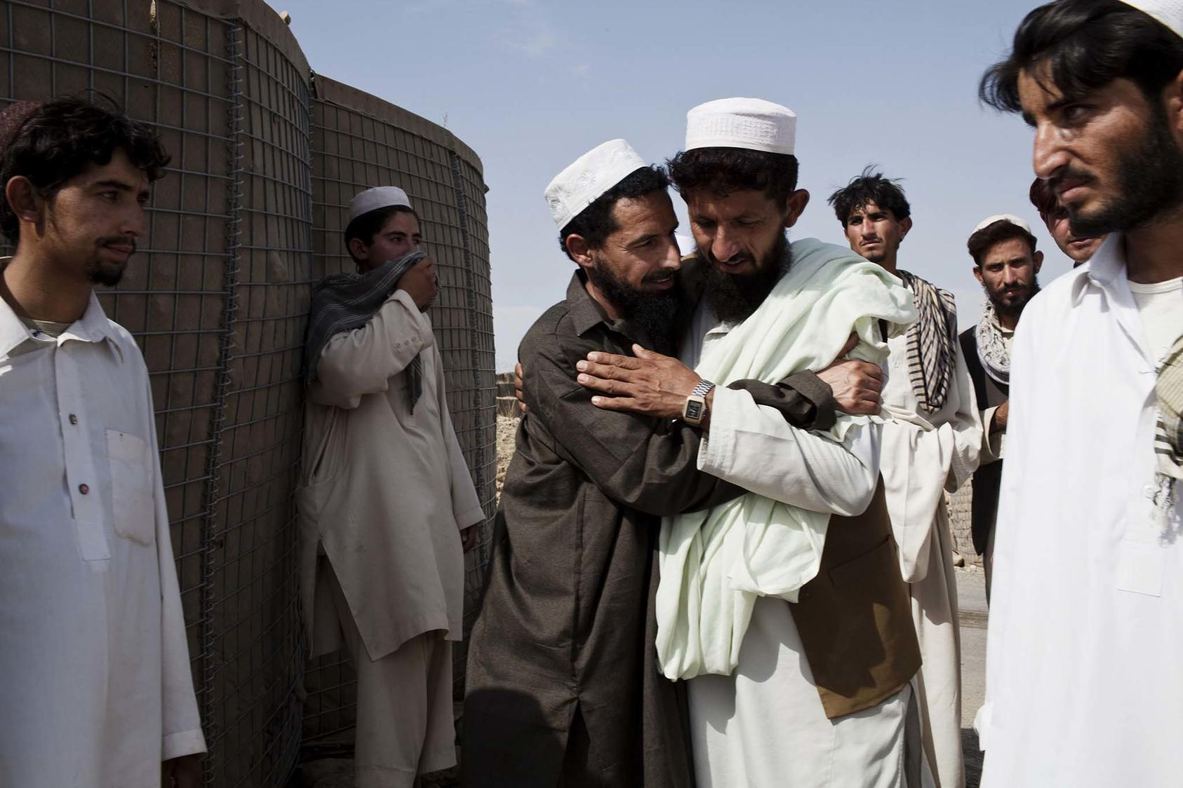 A former detainee is greeted by friends and relatives after his release from a shura at the Operational Coordination Center Provincial in the Khost Province of Afghanistan. (Photo Credit: Adam Ferguson/New York Times)