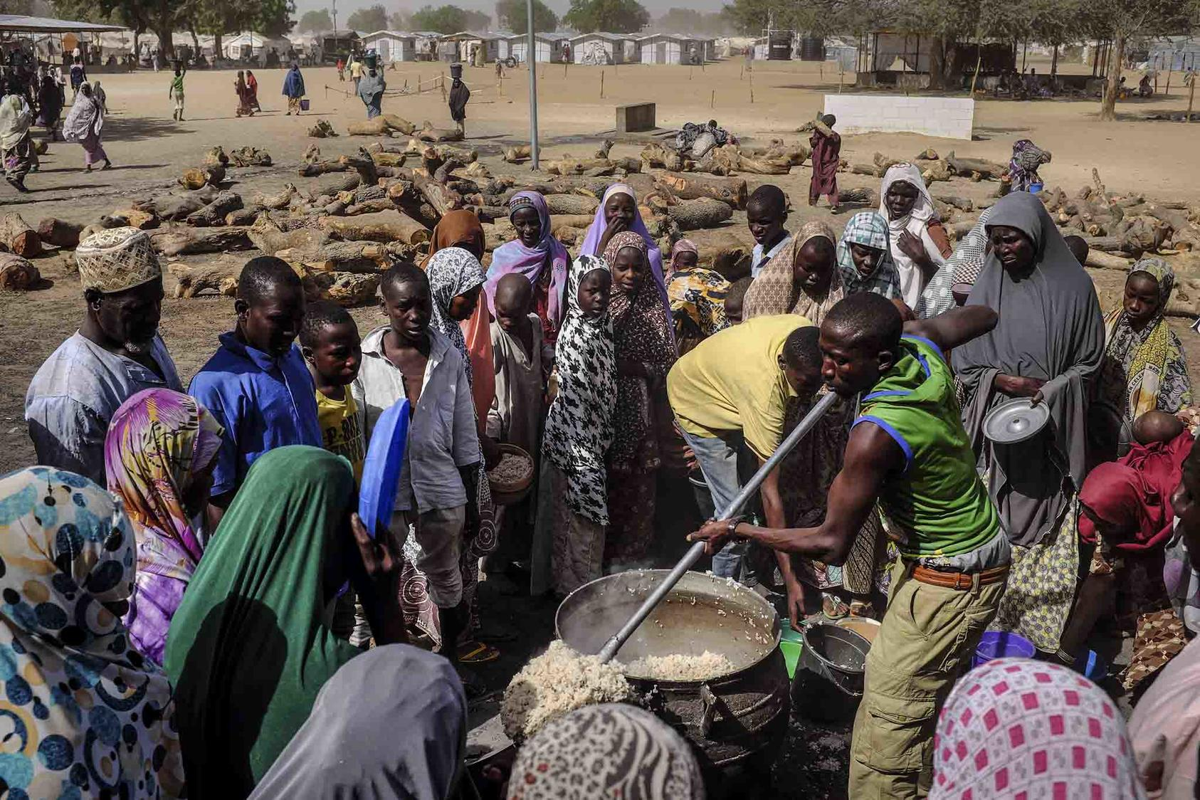 Nigerians uprooted amid the warfare involving Boko Haram receive rice at a camp on the outskirts of the city of Maiduguri in 2016. Nearly 2 million Nigerians are displaced by conflicts in the region. (NYT)