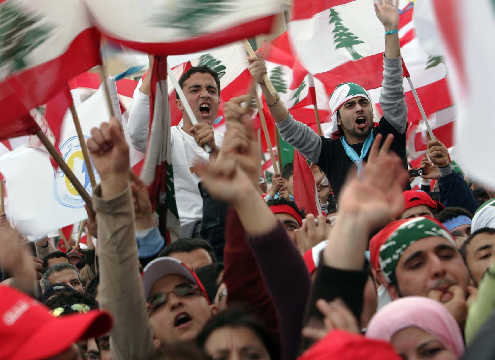 Demonstrators wave the flag of Lebanon during a rally in Beirut. (Shawn Baldwin/The New York Times)