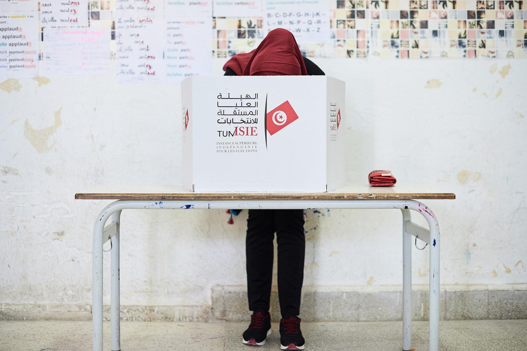 A woman fills out her ballot in the Tunisian election