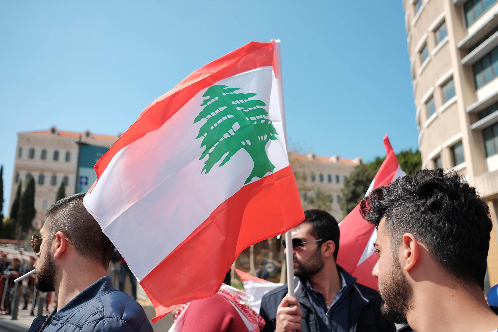 Lebanese protesters with Lebanese flag. (Photo Credit: Jeff Merheb / Shutterstock.com)