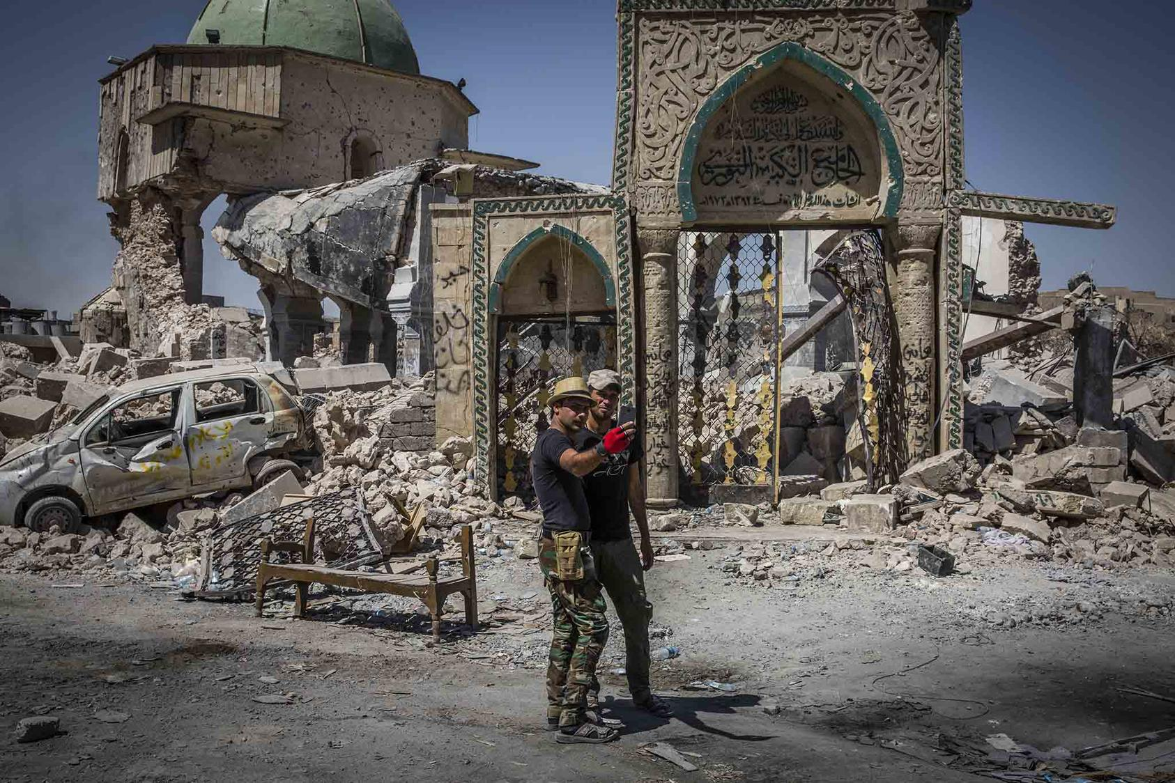 Two people take a selfie in front of a destroyed mosque. (Ivor Prickett/The New York Times)